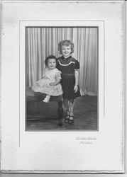 Studio portrait of an unidentified young girl and a toddler, about 1940s