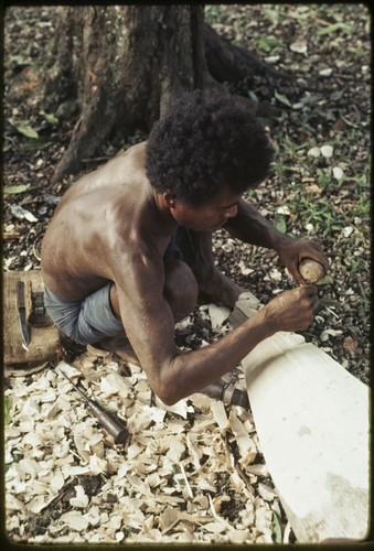 Canoe-building: man carves nipawa (grasshopper) design on prow