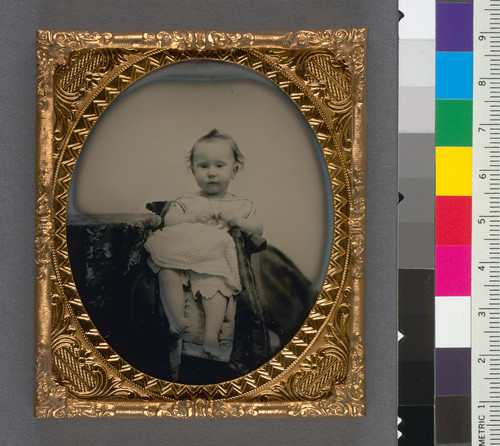 [Unidentified baby touching a gold necklace.]