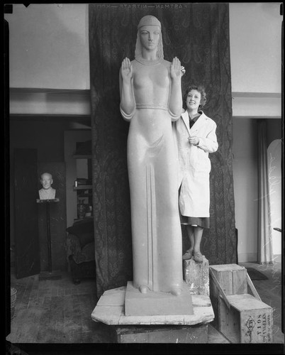 "Artist Ada May Sharlpess next to the model for her sculpture ""Nuestra Reina de Los Angeles"" now in Echo Park, Los Angeles, 1935"
