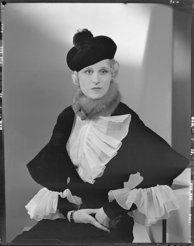 Peggy Hamilton modeling an Adrian gown with ruffles at the wrists and collar and a beret hat, 1933