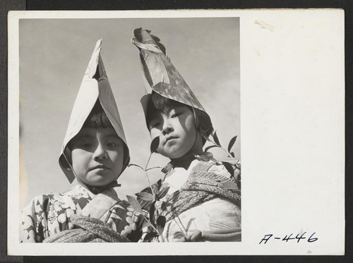 Two of the Nursery School children who participated in the Harvest Festival Parade held at this relocation center. Photographer: Stewart, Francis Newell, California