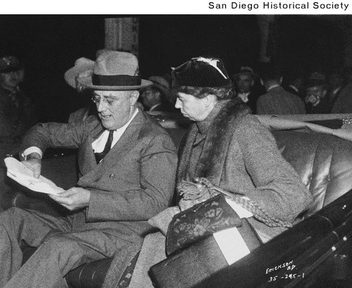 Franklin D. and Eleanor Roosevelt sitting in a car and looking at a piece of paper in Balboa Stadium