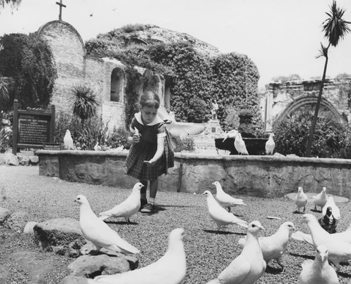 Girl feeding birds at the San Juan Capistrano Mission on the corner of Ortega Highway & Camino Capistrano