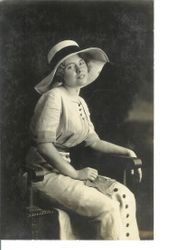 Unidentified young woman seated in chair with large summer hat and linen-like long dress with buttons down front, about 1913