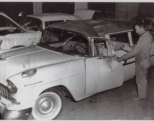 Kenneth R. Torliatt inspects damaged Souza family car, 132 Keller Street, Petaluma, California, January 1961