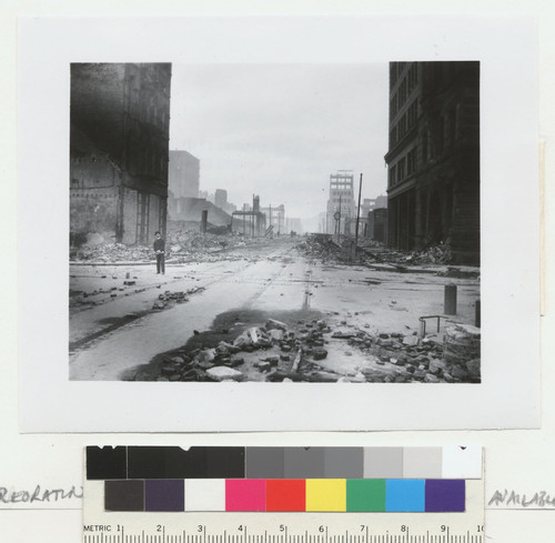 [Man standing in intersection among ruins. Unidentified location.]