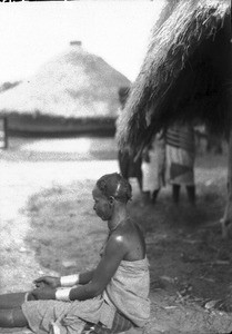 African person sitting in front of a hut, southern Africa