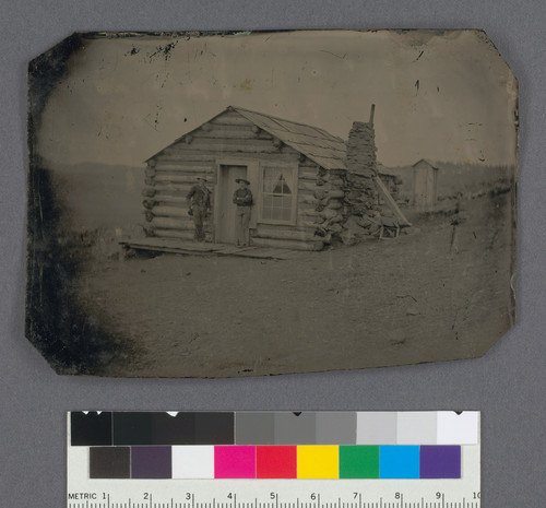 [Two men in front of a log cabin.]