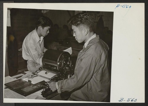 Editor Albert Saijo inspects a copy of Echo, high school paper, being run off on the mimeograph machine by Toyoji Sugita, staff artist and technician. Photographer: Hosokawa, Bill Heart Mountain, Wyoming
