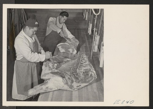 Sam Takeda and George Yoshihara, former west coast butchers, cutting meat for center mess halls. With meat rationing strictly adhered