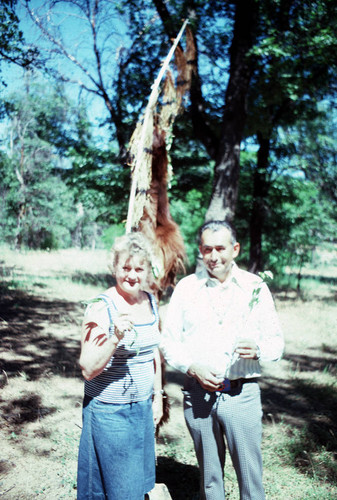 Tom Merino and Dorothy Hill in front of bearskin and maple bark flag at Greenville Bear Dance--1981