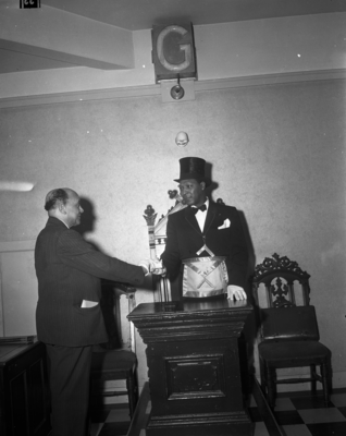 Calisphere: Mason in top hat and masonic apron shaking hand