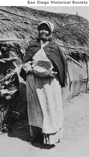 Campo Indian Elaine Quinhitch holding a basket outside a palm frond hut