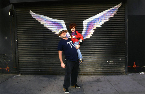 Unidentified man holding a child and posing in front of a mural depicting angel wings