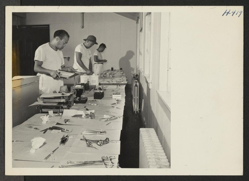 Closing of the Jerome Center, Denson, Arkansas. Dental and surgical instruments are being sorted and labeled in the center's hospital prior to shipment to other center hospitals. Photographer: Mace, Charles E. Denson, Arkansas