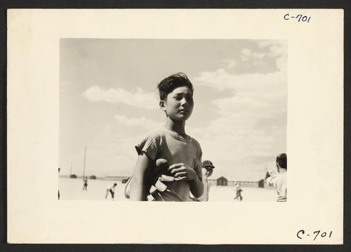 Manzanar, Calif.--Young evacuee baseball player, member of one of the eighty teams which has been organized at this War Relocation Authority center for evacuees of Japanese ancestry. Photographer: Lange, Dorothea Manzanar, California