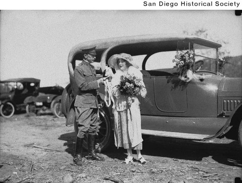 An Army officer presenting a bottle to a woman holding a large bouquet