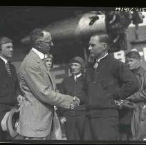 Two men shaking hands with an airplane in the background