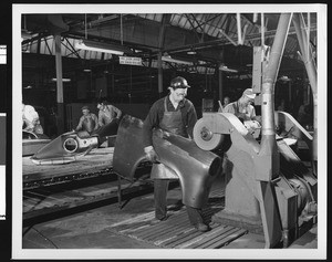 Interior view of an unidentified automobile factory showing workers on an assembly line, ca.1925