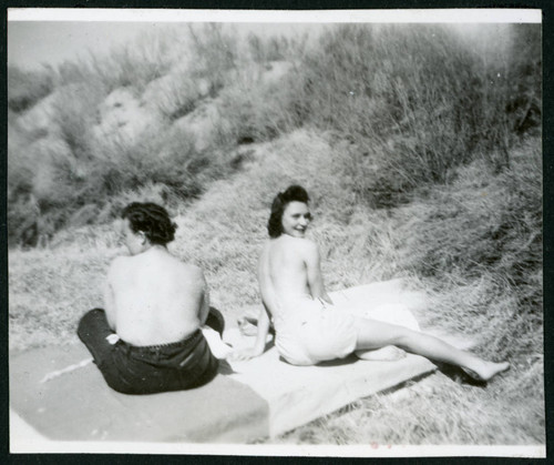 Photograph of two women sunbathing topless near Manzanar