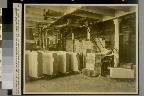Soap chipping room Soap Dept. Bayonne Refinery showing man feeding soap into soap chipping machine which cuts the soap into chips which are delivered into barrels on the floor below
