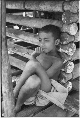 Boy leans against wall of a yam house, with good detail of notched pole construction