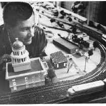 "Ron Gilliland. Caption reads, ""Builder Gilliland dwarfs the State Capitol, above, and stands outside the caboose he built to house the model train exhibit, below."""