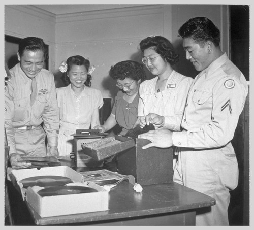 "Selecting records to play for dancing at this Washington USO for servicemen and their friends are: Pfc. Paul Y. Hosoda from Camp Ritchie, Mary Ogawa, formerly from Idaho, Fuki Seki of Seattle and Minidoka, Yukiye Tanaka from California and Granada, and Corporal Jack K. Furuye, Camp Meads, formerly from Los Angeles.--Photographer: Van Tassel, Gretchen--""Washington, D.C."", . 8/11/45"