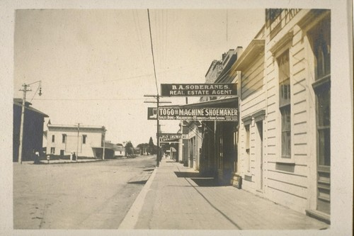 [Street and sidewalk, unidentified location. Businesses include B.A. Soberanes, Real Estate Agent and Togo the Machine Shoemaker.]
