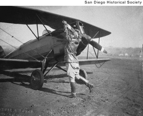 Ruth Alexander preparing to start the motor of a biplane at the Ryan Flying School
