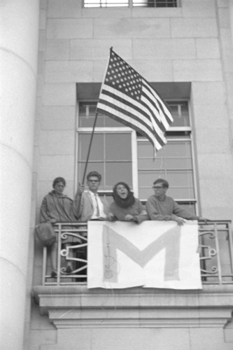 Students on Sproul Hall balcony with flag