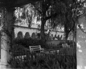A view of the San Fernando Mission showing benches and trees next to a garden walkway