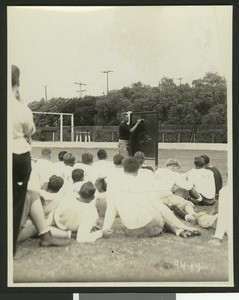 University of Southern California football coach Howard Jones at a football practice, diagramming a play on a chalkboard in front of the football team, Bovard Field, USC campus, 1929