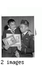 """They're Japanese--but loyal Americans. In 1917, Kaytaro Tsukamoto served with the United States Army. Now a San Francisco businessman, he is commander of the Japanese American Legion Post. Here he shows his 11-year-old son Wilmer pictures of himself when he was an American doughboy of '17. Tsukamoto was born in this country.""--caption on photograph JARDA-1-35"