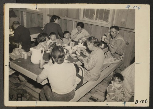 Manzanar, Calif.--Mealtime during early days after evacuation at Manzanar, now a War Relocation Authority center for evacuees of Japanese ancestry. In housing, as well as at meal times, family life is observed. Photographer: Albers, Clem Manzanar, California