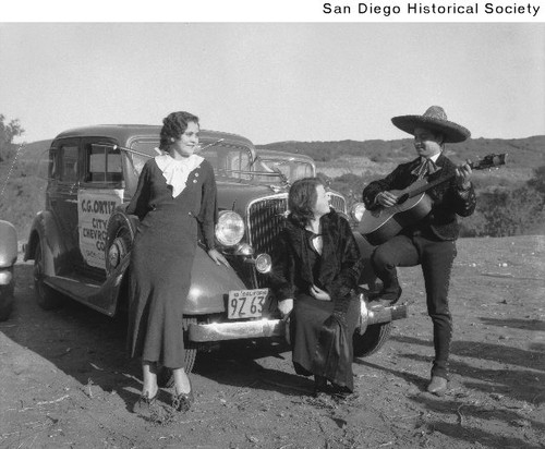 Two women sitting on the front of an automobile while being serenaded by a Mexican singer