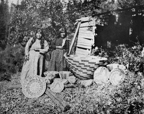 Two Maidu women of the Brownsville area with a various assortment of baskets