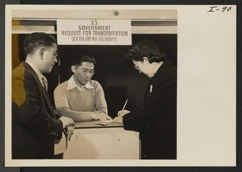 Harry Fuji of the Heart Mountain Relocation Office in charge of transportation, is helping Mr. and Mrs. Thomas T. Sashihara