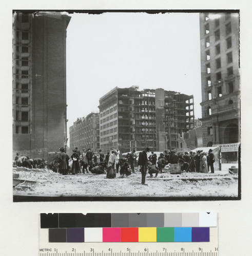 [Crowd searching through rubble. At O'Farrell and Market Sts.? Left to right: Mutual Savings Building, Palace Hotel, Monadnock Building, and Call Building.]