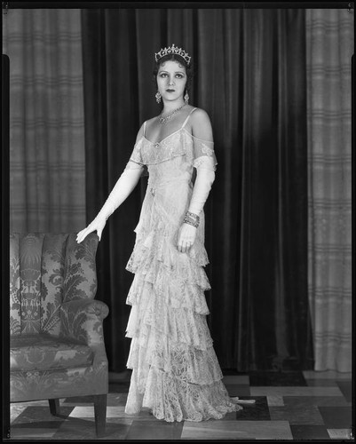 Woman modeling a lace evening gown and crown, circa 1928-1933