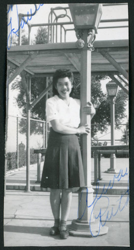 Photograph of Ruth standing next to a lamp post at a swimming pool