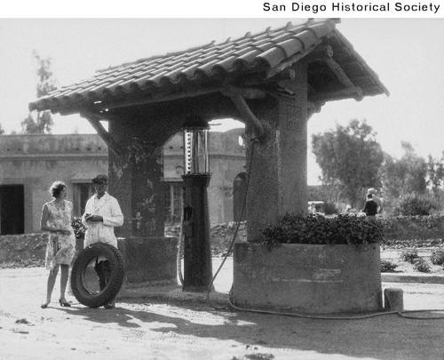 A woman and man in coveralls standing at a Rancho Santa Fe gas station