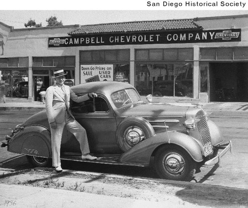 Larry Imig standing next to a Chevrolet automobile parked in front of the Campbell Chevrolet Company