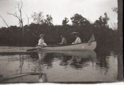 Three people (one man and two women) in small boat on Lake Jonive