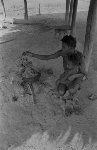 Young woman and infant by the fire, San Basilio de Palenque, 1977