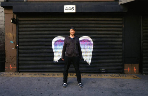 Unidentified man in dark jacket and cap posing in front of a mural depicting angel wings