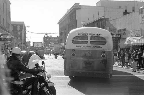 Alameda County sheriffs department school bus with arrestees pulling on to Telegraph Avenue