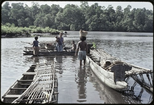 Canoes: women load baskets of yams and other items onto canoe used for coastal transport