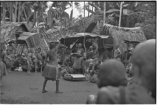 Mortuary ceremony, Omarakana: mourning women and children gathered for ritual exchange of banana leaf bundles